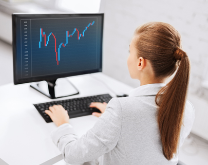 Woman looking at a forex chart on a computer.